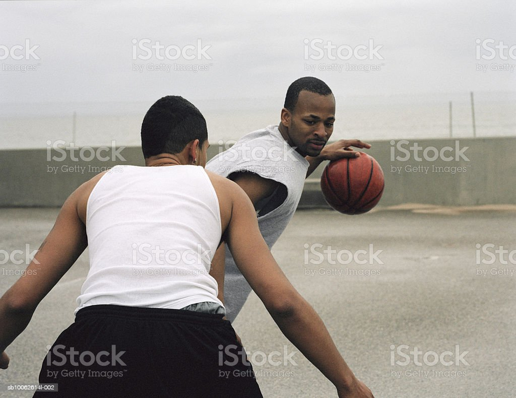 Two young men playing basketball foto de stock libre de derechos