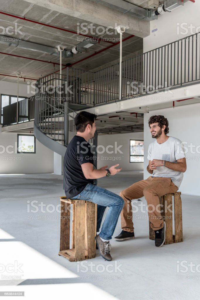Two young men talking in an empty office and telling jokes stock photo