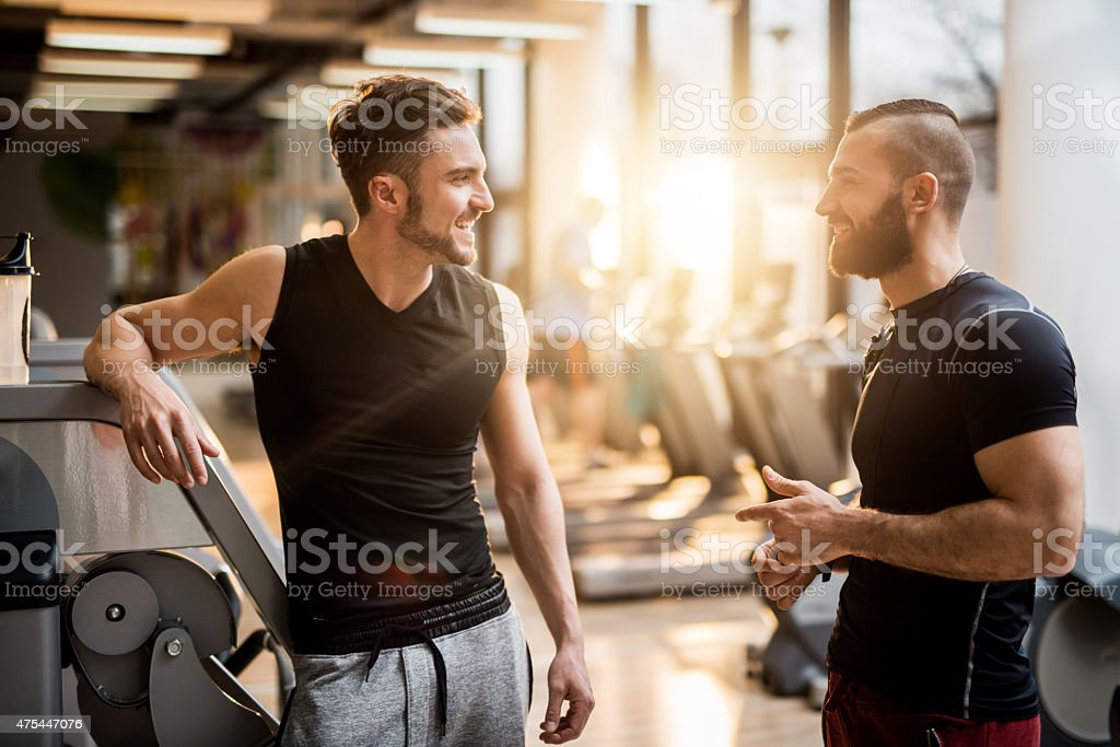 Two young men talking to each other in health club. stock photo