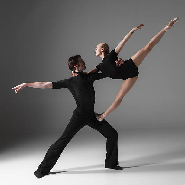 two young modern ballet dancers on gray studio background The two young modern ballet dancers in black suits posing over gray studio background  male animal stock pictures, royalty-free photos & images