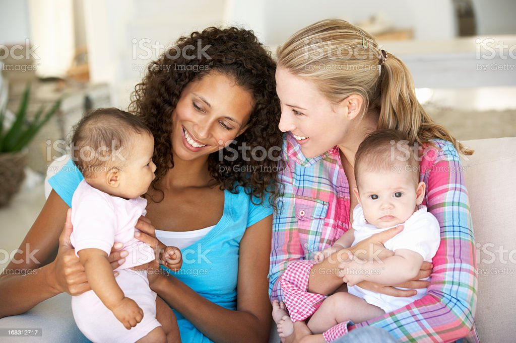 Two Young Mothers Sitting On Sofa At Home with their babies stock photo