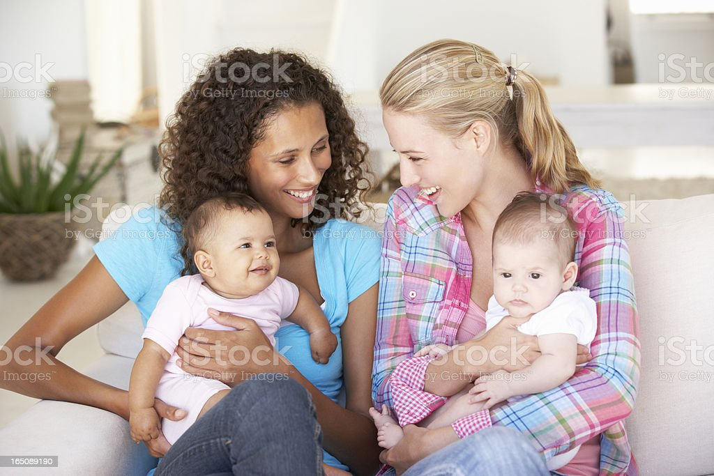 Two Young Mothers With Babies At Home stock photo