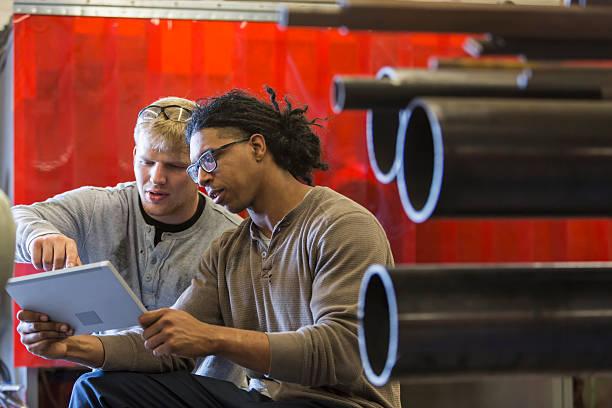 two young multi-ethnic men using digital tablet - suministros escolares fotografías e imágenes de stock