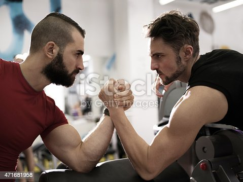 Profile of two serious young men arm wrestling in a health club.