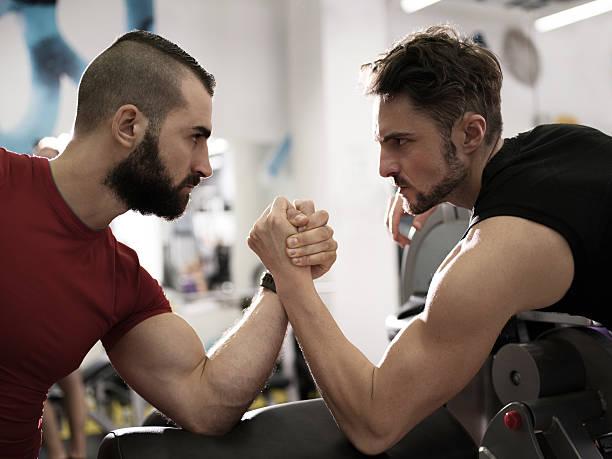zwei jungen muskulös männer armdrücken im fitnessraum. - armdrücken stock-fotos und bilder