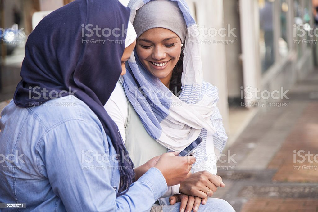 Two young muslim women laughing at text message. stock photo
