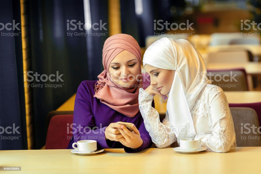 two young Muslim women sitting in a cafe and looking for something in a cell phone stock photo
