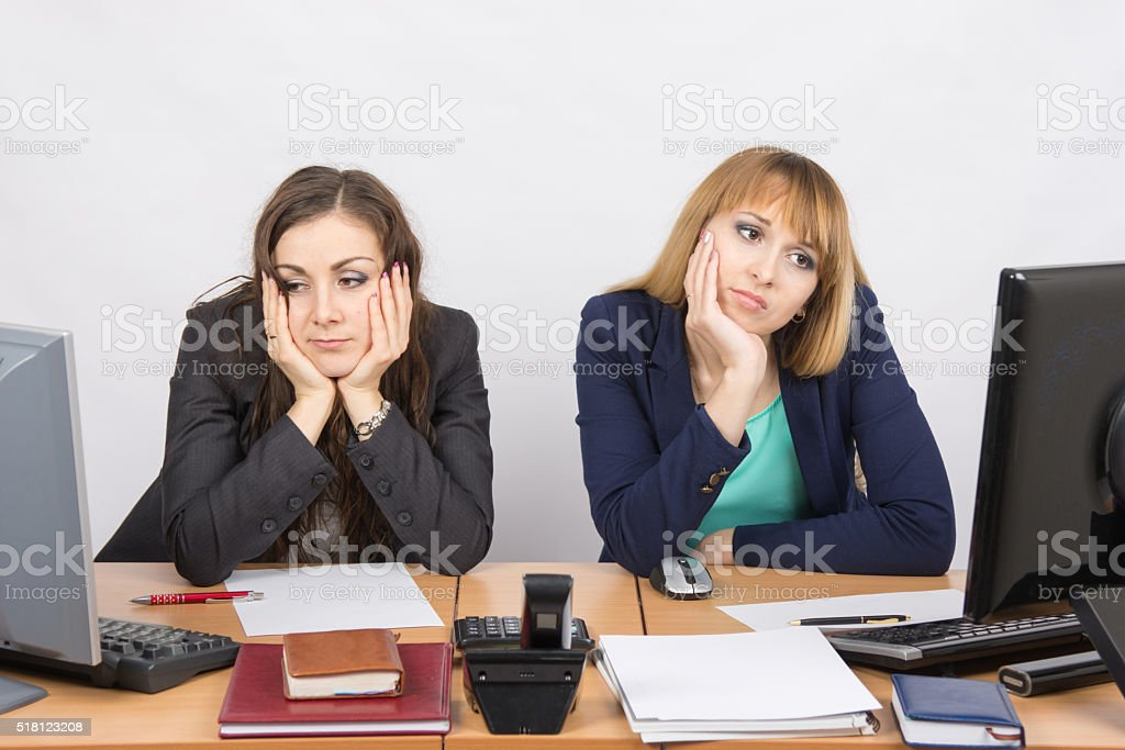 Two young office worker tired sitting in front of computers stock photo