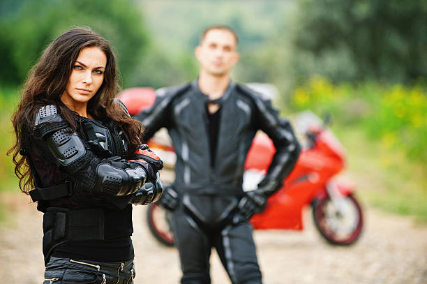 two young people against red motorbike stock photo