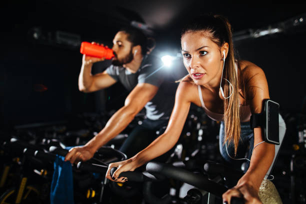 Two young people exercising on exercise bike at gym stock photo