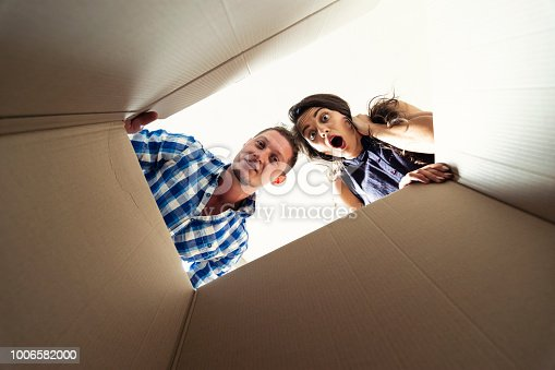 istock Two young people looking surprised into a carton box 1006582000
