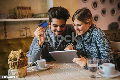 Two young people are shopping online using digital tablet and paying with credit card during coffee break in a cafe.