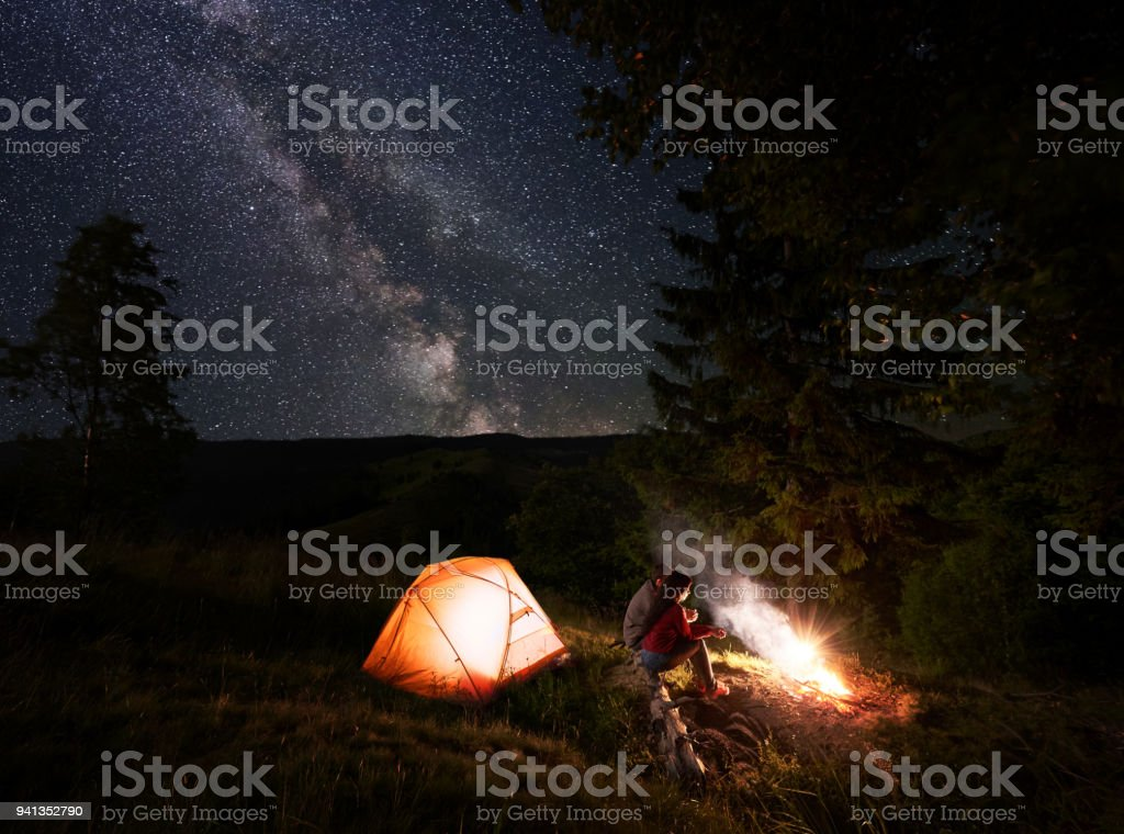 Two young people sit on log near burning fire near tent under powerful fir-tree above the starry sky stock photo