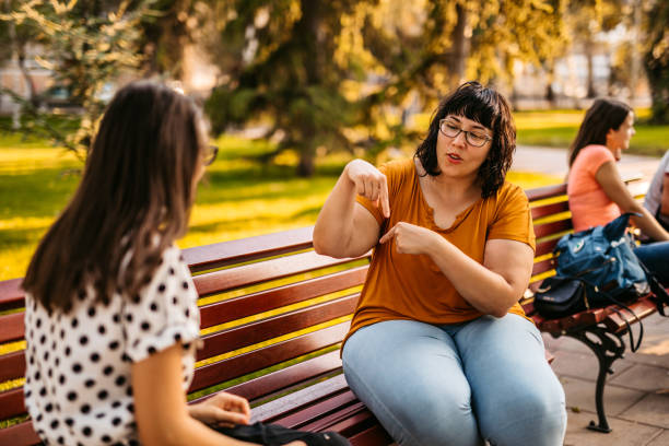 Two young people speak in sign language stock photo