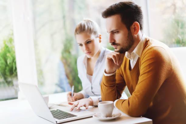 zwei junge menschen, die mit einem laptop, problemlösung - www kaffee oder tee stock-fotos und bilder