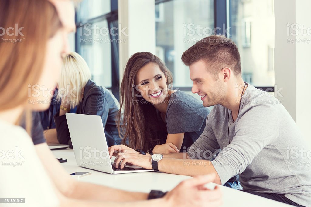 Two young people working on laptop together Start-up business team. Focus on two happy young people working on laptop together. 20-24 Years Stock Photo