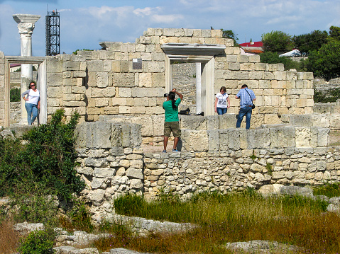 Topic - World Photography Day. Photo portrait in  frame formed by doorway  on ruins of Chersonesos, Sevastopol, Russia, June 10, 2016 .