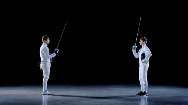 Two Young Professional Fencers Greet Each Other, and Preparing for Fighting Match. Shot Isolated on Black Background. stock photo