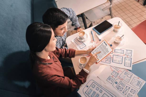 zwei junge vielversprechende wissenschaftler diskutieren energie forschung - produktdesigner stock-fotos und bilder