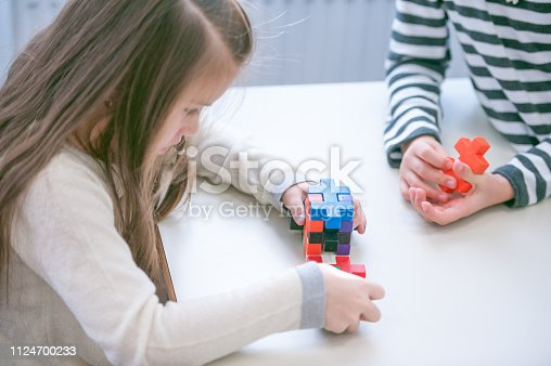 Two Young Schoolgirls Playing with Colorful Puzzle Cube in the Clasroom During School Break