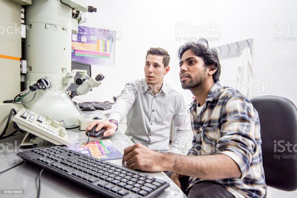 Dos jóvenes científicos sentado detrás de escritorio usando la computadora - foto de stock