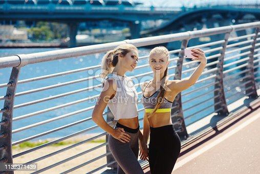 istock Two young sexy sports girls take a selfie on the phone on a city street. Smiling looking at the camera. Healthy lifestyle. Women Friendship 1132371439