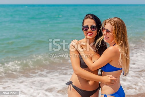 700603062istockphoto Two young sexy stunning women walking having fun smiling 584479512
