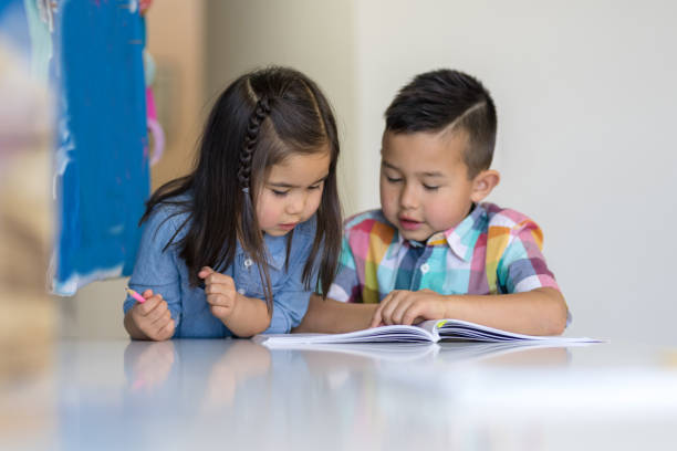 Two young siblings do homeschooling together at their desk stock photo