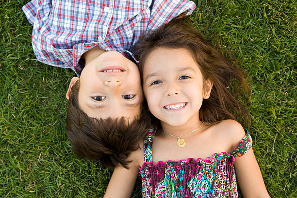 Two young siblings lying on the grass smiling together stock photo