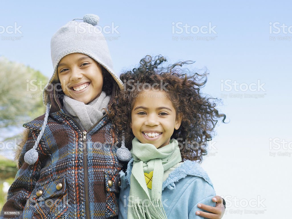Two young sisters hugging in winter stock photo