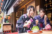 浴衣のかき氷を食べることで若い 2 人の姉妹の氷デザート