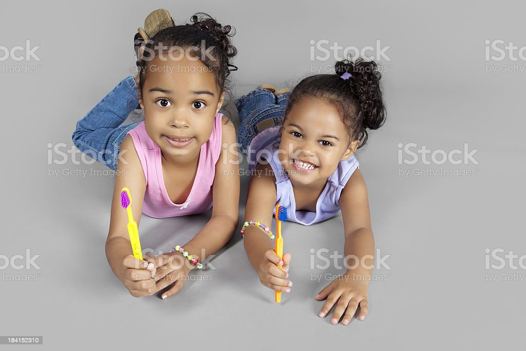 Two young sisters with toothbrushes royalty-free stock photo