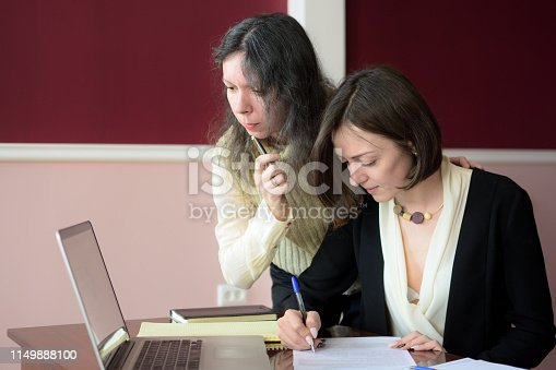 young smartly dressed lady discusses issues with another young smartly dressed lady, points to a laptop and suggests a solution, vintage office room, vintage office desk