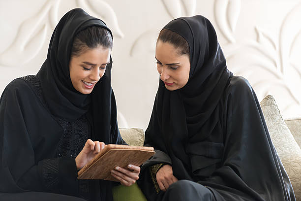 Two Young Smiling Emirati Women in Abaya Reviewing Digital Tablet stock photo