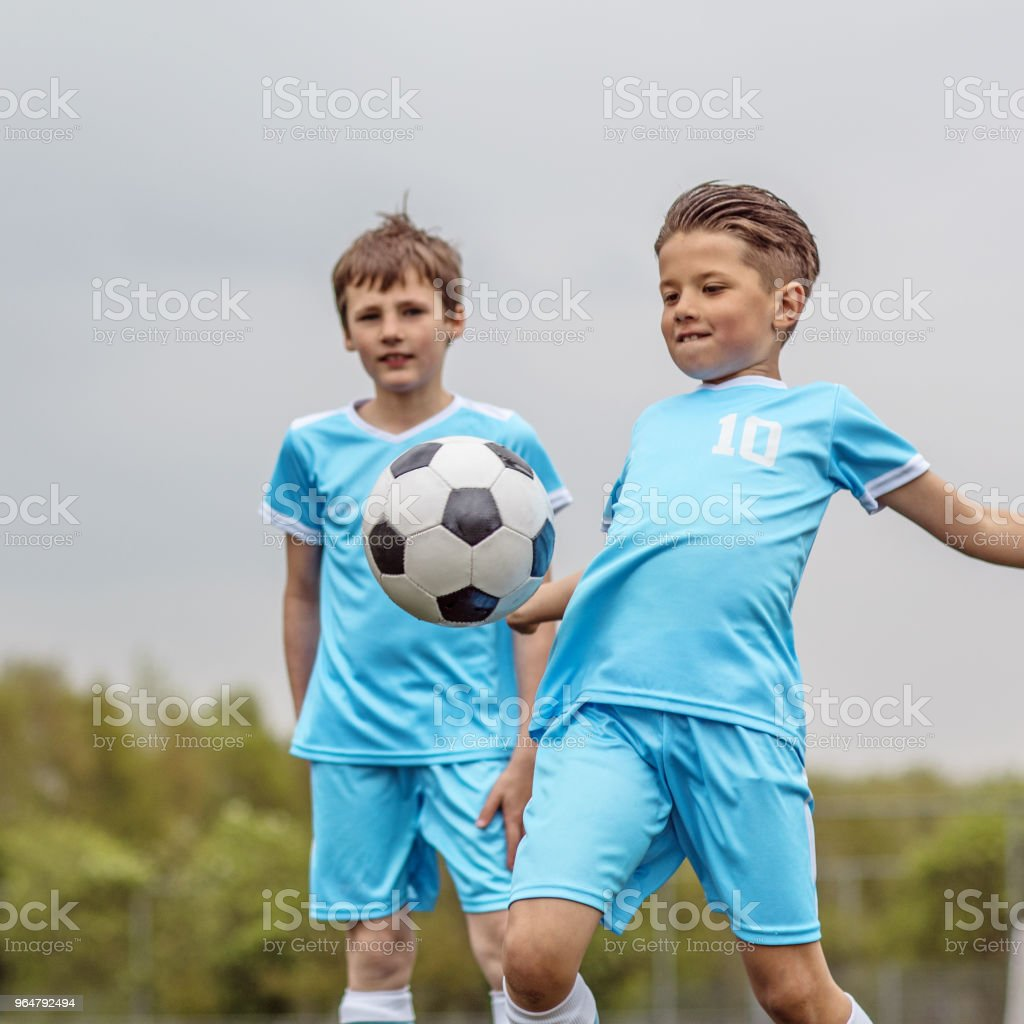 Two young soccer player boys posing for a photo during a football training session royalty-free stock photo