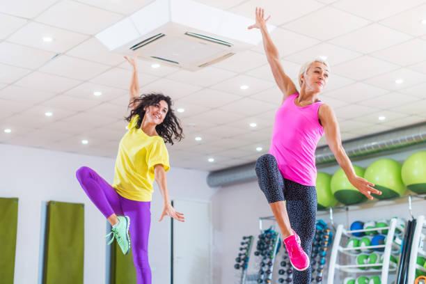 Zwei junge sportliche Frauen im Fitness-Studio trainieren, tanzen, tun, Cardio, arbeiten an Gleichgewicht und Koordination. – Foto