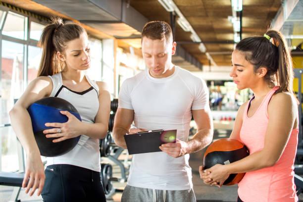 zwei junge sportliche frauen mit fitnessbällen nach anweisungen ihres personal trainers im fitnessstudio. - trainingsplan frauen stock-fotos und bilder