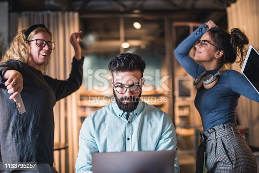 istock Two young students dancing while man student training to work at laptop. 1133795257