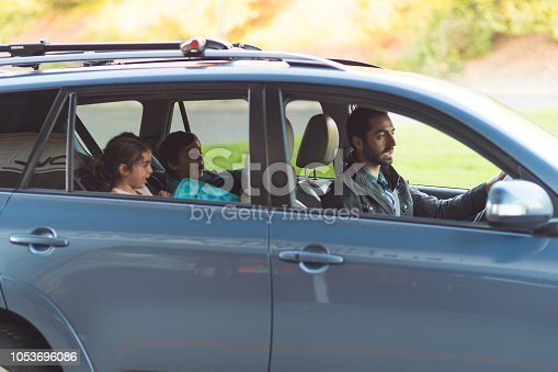 A pair of young siblings sit in the back seat of their car after getting picked up from school by their father.