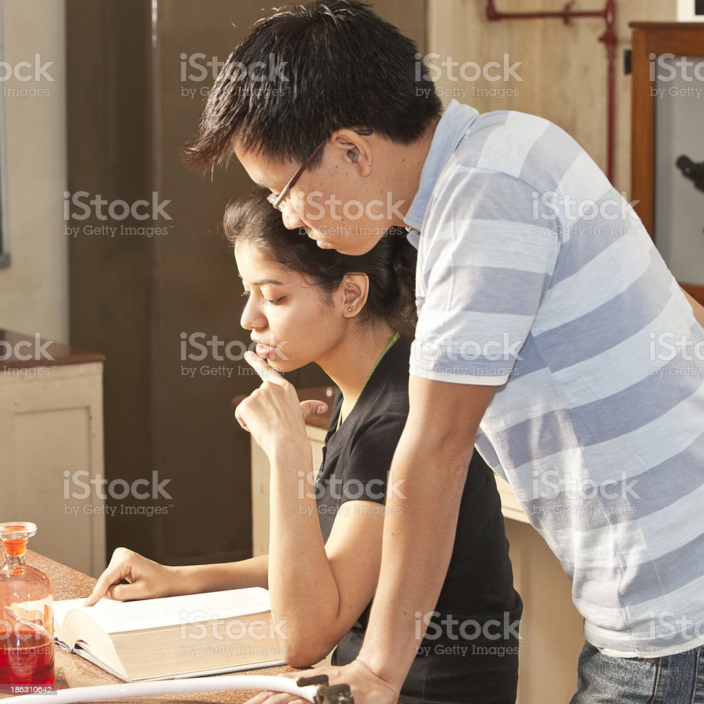 Two young students reading book together in Delhi, India royalty-free stock photo