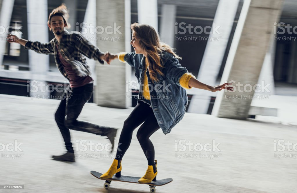 Two Young Teenagers Holding Hands, Skateboarding stock photo