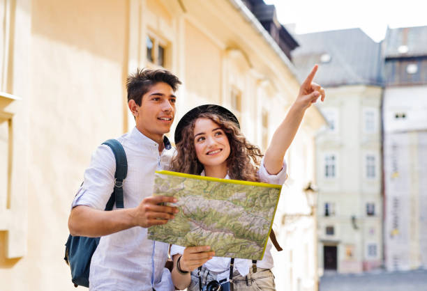 Two young tourists with map and camera in the old town stock photo