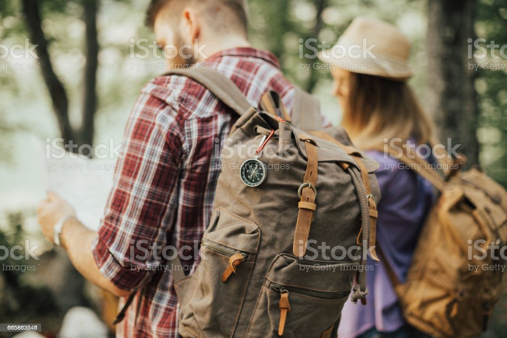 Two young travelers looking at the map stock photo
