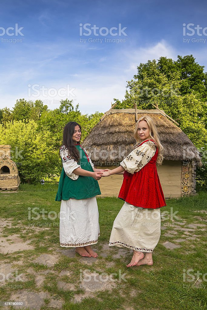 Two young ukrainian women in national costumes at the yard stock photo