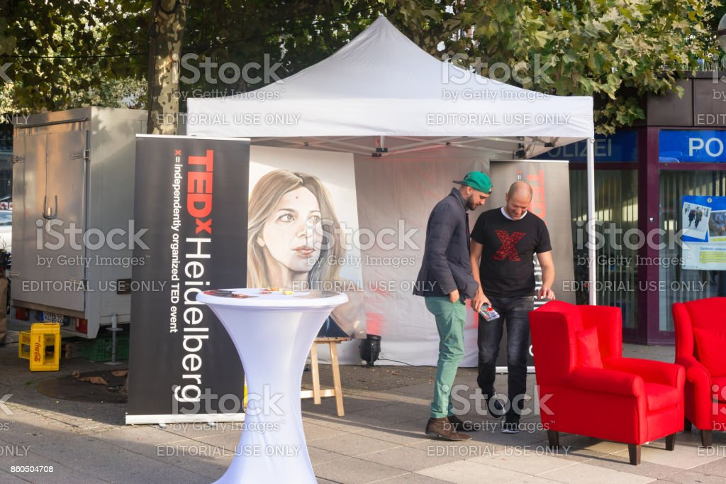 Two young unidentified men promote an TEDx event in the Heidelberg city at the TED tent middle on the street. HEIDELBERG, GERMANY - October 1st 2017.