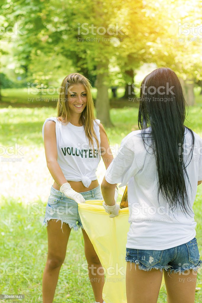 Two young volunteers picking garbage stock photo