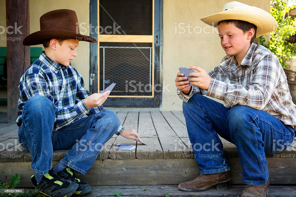 Two young western brothers playing cards on porch stock photo