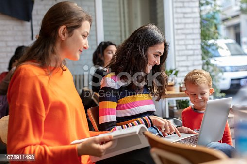 1043434558 istock photo Two Young Woman and Little Boy Looking at Laptop in a Cafe Shop 1078911498