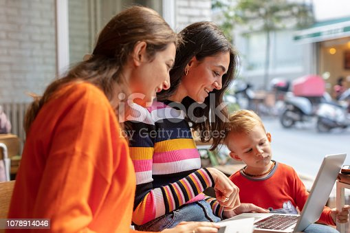 1043434558 istock photo Two Young Woman and Little Boy Looking at Laptop in a Cafe Shop 1078914046