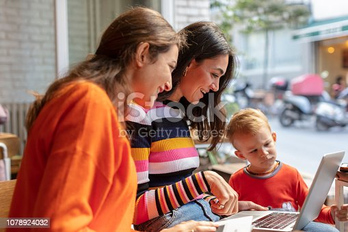 1043434558 istock photo Two Young Woman and Little Boy Looking at Laptop in a Cafe Shop 1078924032